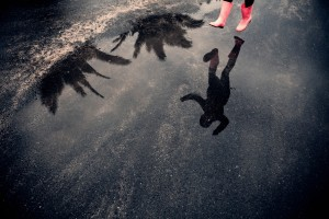 Reflection of person in rubber boots jumping over puddle